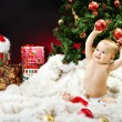 Christmas baby sitting on fur holding red ball — Stock Photo #14449319