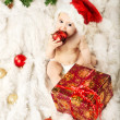 Christmas baby in red hat sitting on fur and eating gift — Stock Photo