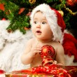 Christmas baby in hat holding red ball near gift box — Stock Photo