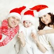 Christmas family of three persons in red hats — Stock Photo