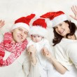 Christmas family of three persons in red hats. Hapy parents — Stock Photo