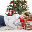 Christmas gift. Smiling happy man sleeping in front of fir tree — Stock Photo