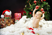 Christmas baby sitting on fur holding red ball — Stock Photo