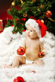 Christmas baby in hat sitting on fur holding red ball — Stock Photo