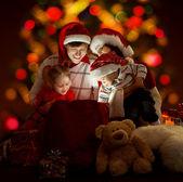 ευτυχισμένη οικογένεια τεσσάρων ατόμων σε κόκκινα καπέλα άνοιγμα φωτισμού τσάντα — Φωτογραφία Αρχείου