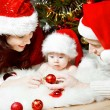 Christmas family of four persons in red hats giving gifts — Stock Photo