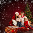 Christmas family of four persons and fir tree with gift boxes - Stock Photo