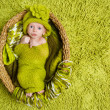 Newborn baby in woolen hat over green background — Stock Photo