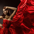 Woman in red dress dancing with flying fabric — Stock Photo #15433253
