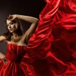 Woman in red dress dancing with flying fabric — Stock Photo