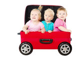 Group of kids driving in suitcase car — Stock Photo