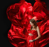 Pregnant woman in red evening dress flying on wind — Stock Photo