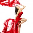 Woman in red dress dancing with fabric — Stock Photo #19950157