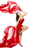 Woman in red dress dancing with fabric — Stock Photo
