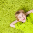 Child lying on the green carpet background. — Stock Photo