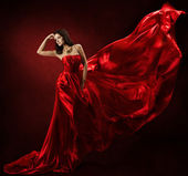 Woman in red waving dress dancing with flying fabric — Stok fotoğraf