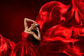 Woman in red dress blowing with flying fabric, fashion girl posing silk fluttering cloth — Stock Photo