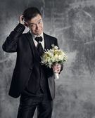 Thoughtful groom with flowers bouquet. Gray background. — Stock Photo
