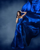 Woman in blue dress with flying blue silk fabric — Stock Photo