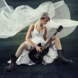 Bride playing rock guitar over artistic dark background — Stock Photo