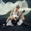 Bride playing rock guitar over artistic dark background — Stock Photo #26090067