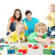 Happy family. Parents with three kids playing blocks over white — Stock Photo