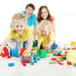 Happy family. Parents with two kids playing blocks over white — Stock Photo #26115919