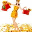 Autumn woman with shopping bags in dress of maple leaves. White background — Stock Photo