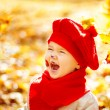 Happy smiling child in autumn park enyoing sunshine — Stock Photo