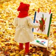 Child drawing on easel in yellow Autumn Park. Creative kids — Stock Photo #30886241