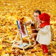 Mother and child drawing on easel in yellow autumn park. Creative kids — Stock Photo #30886243