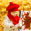 Stock Photo: Child drawing on easel in yellow Autumn Park. Creative kids