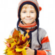 Child in woollen clothes with yellow autumn leaves — Stock Photo