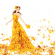 Autumn woman in fashion dress of maple leaves holding bouquet l — Stock Photo
