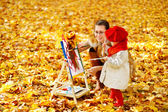 Mother and child drawing on easel in yellow autumn park. Creative kids — Stock Photo