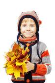 ребенка в шерстяную одежду с желтые осенние листья — Стоковое фото