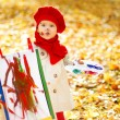 Stock Photo: Child drawing on easel in yellow Autumn Park. Creative kid