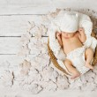 Newborn baby sleeping in basket on leaves over white — Stock Photo #31839835