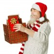 Christmas old man helper with beard in red hat carrying present box — Stock Photo #32328079