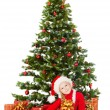 Christmas helper child in Santa hat sitting under fir tree — Stock Photo