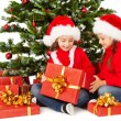 Christmas kids in Santa hat open gift box — Stock Photo