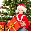 Christmas child open gift box, sitting under fir tree — Stock Photo