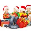 Christmas helpers kids in Santa hat holding presents — Stok fotoğraf