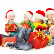 Christmas helpers kids in Santa hat holding presents — Stockfoto