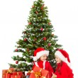 Christmas helpers kids in Santa hat open gift box under fir tree — Stock Photo