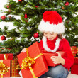 Christmas child  open gift box under fir tree,  — Lizenzfreies Foto