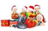 Christmas helpers kids in Santa hat holding presents — Stock Photo