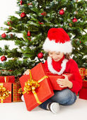 Christmas child open gift box under fir tree, — Stock fotografie