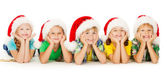 Christmas kids smiling in Santa red hat lying down — Stock Photo