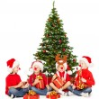 Christmas helpers kids in Santa hat playing under fir tree over white background — Stock Photo